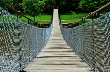 Crossing Over. Swinging footbridge beckons the adventurous hiker to discover what lies on the other side. Swinging Bridge Park. Croswell, Michigan.