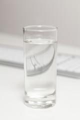 Glas Wasser auf Schreibtisch