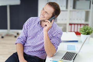 freundlicher geschäftsmann mit telefon und laptop