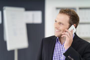 lächelnder geschäftsmann telefoniert im büro