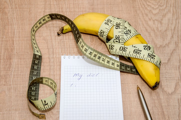 Diet concept with fruit, notebook and measuring tape on wooden table