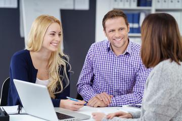 lächelndes junges paar in einem gespräch mit einer kundenberaterin