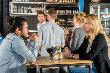 Friends Talking At Table In Bar