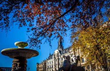 Wittelsbacher Brunnen in München vor der prächtigen Fassade der alten Börse an einem wolkenlosen Herbsttag