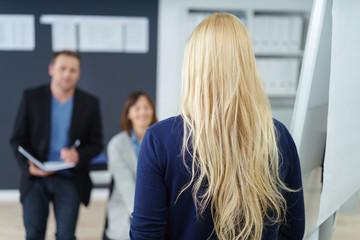 geschäftsfrau hält einen vortrag vor kollegen im büro