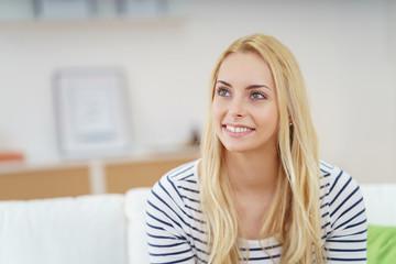 schöne frau mit blonden haaren sitzt entspannt auf dem sofa