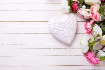Flowers in pink colors and white decorative heart  on white wood