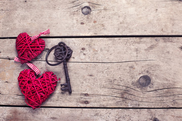 Two red decorative  hearts and key on vintage wooden background