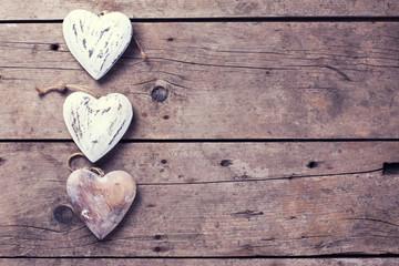Three decorative  hearts on vintage wooden background.