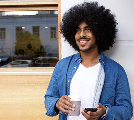 Man with afro standing outside with mobile phone ad coffee.