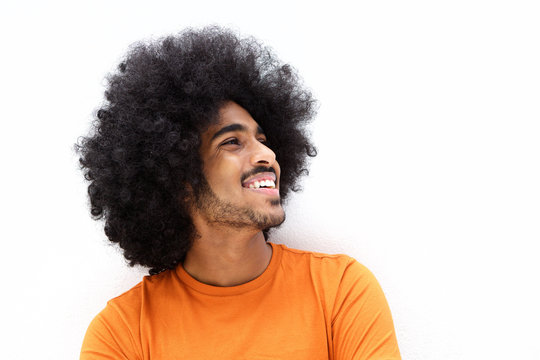 Smiling young man with cool hair looking away