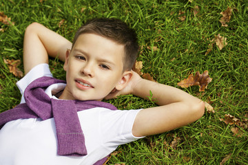 Brunette little boy laying on the grass in the park