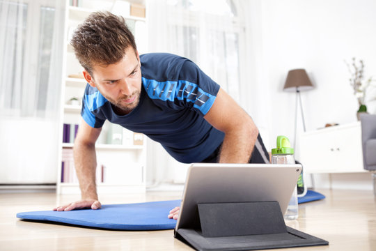 Man Doing Planking While Watching Movie on Tablet