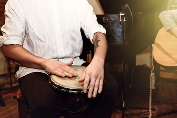 stylish percussionist playing on leather drum on a concert, hand