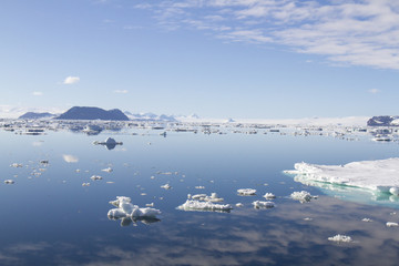 Clouds reflecting in calm seas of Antarctic Sound on sunny day.