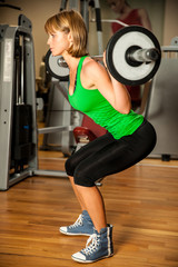 attractive young woman is engaged in fitness sport club working
