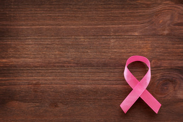 Pink ribbon - symbol of breast cancer awareness. Wooden background.