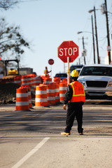 worker holding stop sign in construction site on the street