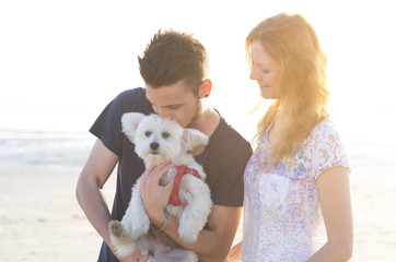 Loving couple is playing with their dog at the beach - caucasian people - people, animal, lifestyle and nature concept