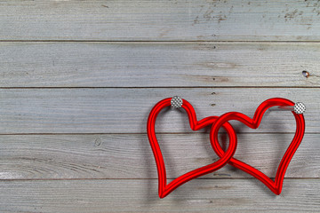 two linked red hearts against the planks background