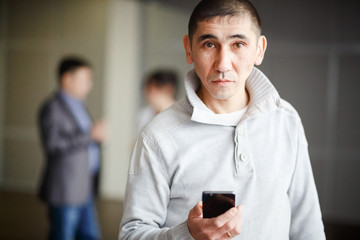 Middle Asian man short haircut with phone in his hand questioning look directly into camera, gets a job. Against background of business men discussing employment. Unemployment, human resources.
