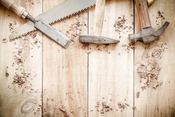 carpenter tools,hammer,nails,shavings, and chisel on wooden back