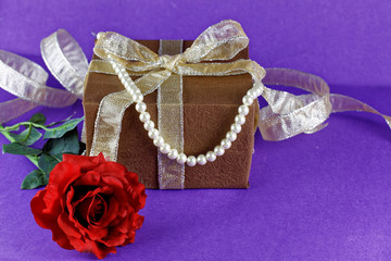 red rose with brown present. Holiday theme