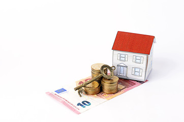 Euro banknote and coins stack with key and paper house for mortg