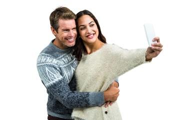 Happy couple wearing warm clothing taking selfie