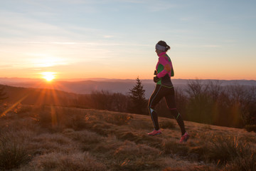 young woman running on the trail in the morning with sunrise and sun flares