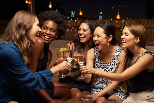 Group Of Female Friends Enjoying Night Out At Rooftop Bar