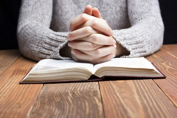 Woman hands praying with a bible in dark over wooden table