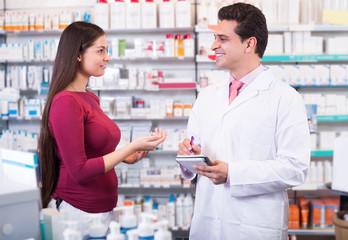 Professional pharmaceutist in drugstore helping girl