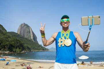 Hashtag gold medal athlete posing for a selfie with his mobile phone on a selfie stick at Sugarloaf Mountain in Rio de Janeiro, Brazil