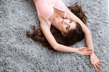 Attractive girl with long brown hair lying on grey carpet