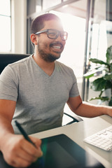 Happy graphic designer working in his office