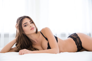 Pretty woman in sexy lingerie lying on the bed