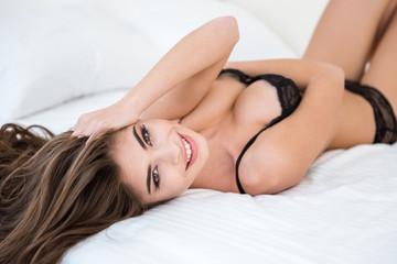 Woman in lingerie relaxing on the bed