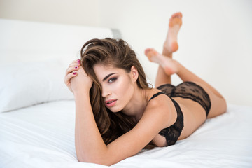 Woman in lingerie and long hair lying on the bed