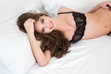 Smiling pretty woman in sexy lingerie lying on the bed