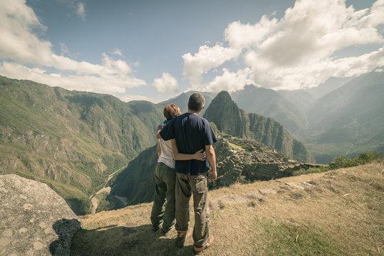 Hugging couple looking at Machu Picchu, Peru, toned image