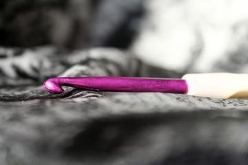 Detailfoto einer lila Häkelnadel auf Musterstoff