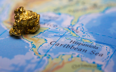 Close-up of a gold nugget on top of a map of Mexico