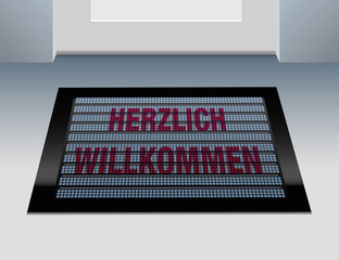 Doormat that says, that you are welcome in german language: Herzlich willkommen.