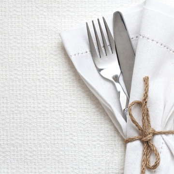 Knife and fork with white linen