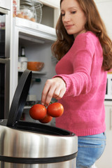 Woman Throwing Away Out Of Date Food In Refrigerator
