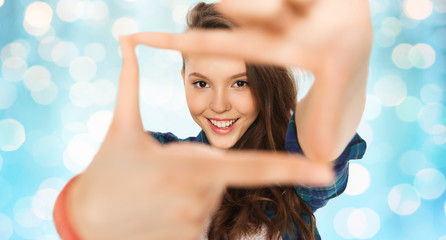 happy teenage girl making frame of fingers