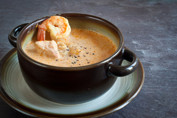 Icelandic fish soup with salmon and prawns. Served on a stone slate table.