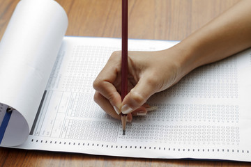 hand of women holding pencil on Standardized test form with answ