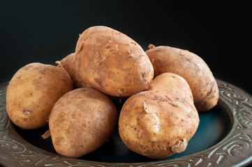 Plate of home grown potatoes piled on a rustic dish on a black table.